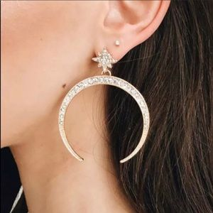 Gold stud earrings shaped like the moon with gems